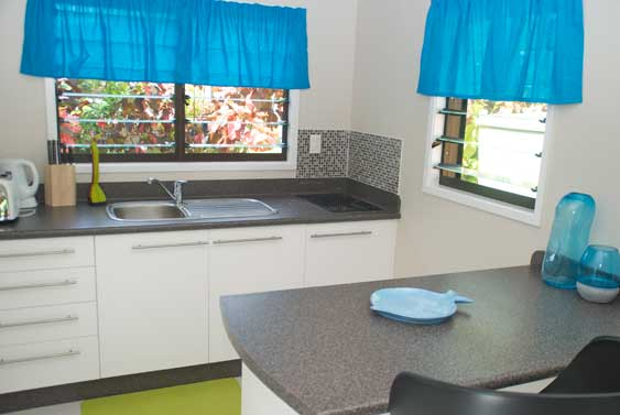 a modern open kitchen and bathroom at the back at Lyas Bungalows