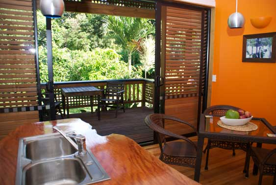 from the kitchen with wood benchtop thru the sliding doors to the fron veranda at Villa Rarotonga Holiday Home